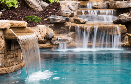 Free form custom swimming pool and stacked stone raised spa features boulder walls, and a gorgeous field stone waterfall that includes a stone bench under the waterfall.