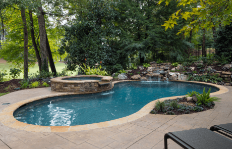 Backyard remodel in Johns Creek includes a free form custom swimming pool and stacked stone raised spa with a waterfall spillover, underwater stone bench, flagstone coping and boulder waterfall. The patio is decorative stamped concrete and overlooks the golf course.