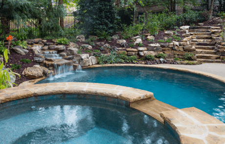 Free form pool with a stacked stone raised spa and waterfall spillover, a boulder waterfall, flagstone coping and Verona 'Boticas pool tile. The Crab Orchard TN Flagstone Stepper pathway and native landscaping blends perfectly with the natural surroundings.