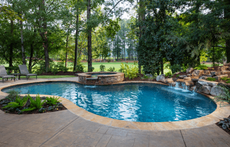 Free form custom swimming pool features a circular stacked stone raised spa with a waterfall spillover, underwater stone bench, flagstone coping and boulder waterfall. The patio is decorative stamped concrete and overlooks the golf course.