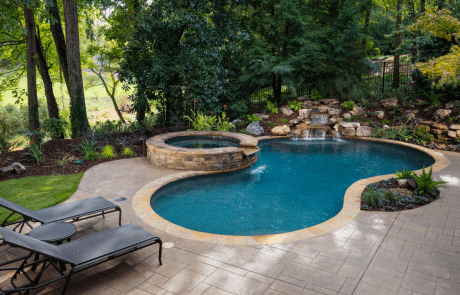 Backyard renovation includes a decorative stamped concrete patio and free form custom swimming pool with a stacked stone raised spa, waterfall spillover, underwater stone bench, flagstone coping and boulder waterfall.