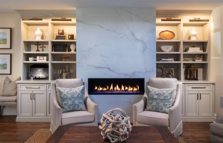 Keeping room renovation includes a dramatic white porcelain slab surround with linear fire feature and custom built-in cabinetry and trim work, and brown hardwood floors.