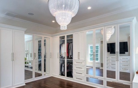 Second story addition includes large private dressing room and master closet with ample storage, white custom cabinetry and mirrored doors with polished nickel hardware and stunning two-tier chandelier. Walls are painted in Dove Wing by Benjamin Moore.