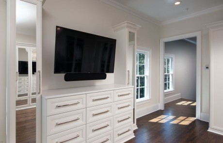 Second story addition with large private dressing room, white custom cabinetry with polished nickel hardware and mounted tv, brown hardwood flooring, and walls painted in Dove Wing by Benjamin Moore.