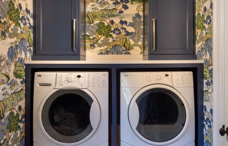 Blue, green & white laundry room addition with side-by-side washer & dryer, blue custom shaker cabinets, bronze hardware, white hexagon porcelain mosaic floor, a hanging drying station, hidden ironing board and broom closet.