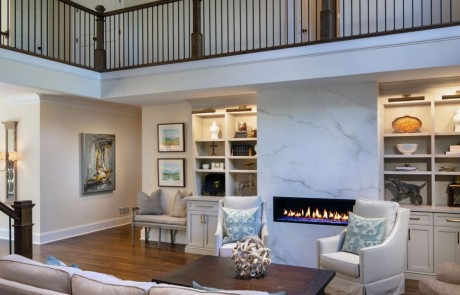 Keeping room renovation includes a floor to ceiling porcelain slab linear fire feature and custom white built-in cabinetry and trim work, brown hardwood floors and new staircase with brown hardwood steps and black metal balusters.