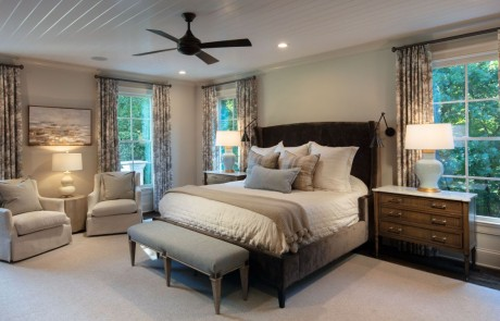 Transitional style, neutral colored master bedroom painted in Benjamin Moore's Edgecomb Gray with white trim work, white painted tongue-and-groove ceiling, secret hidden door, dark bronze wall sconces and ceiling fan, brown hardwood floors and designer finishes.