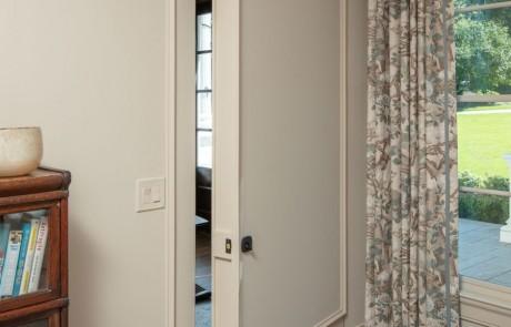 Master bedroom with secret hidden door, custom wall paneling and trim work in Benjamin Moore's Edgecomb Gray.