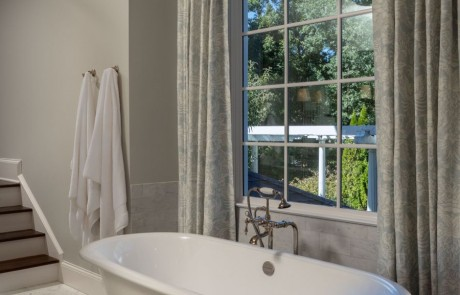Free standing white soaking tub with polished nickel freestanding tub filler, white marble floor, gray walls, and silver semi flush mount ceiling light.