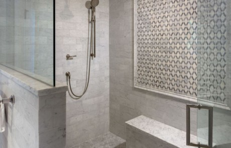 Large frameless glass shower & seating bench with polished nickel fixtures, Carrera Bianco marble tile walls and ceiling and gray marble lattice mosaic accent wall.