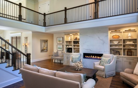 Keeping room remodel includes a floor to ceiling porcelain slab linear fire feature and custom white built-in cabinetry and trim work, brown hardwood floors and new staircase with brown hardwood steps and black metal balusters.