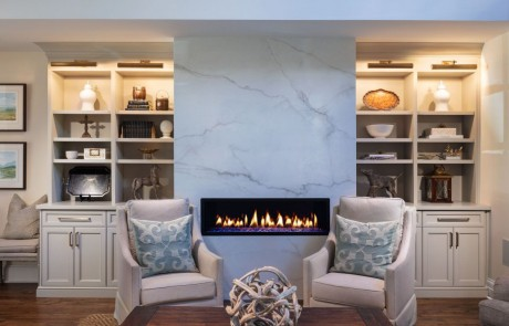 Keeping room renovation includes a seating area with a white porcelain slab surround and modern linear fire feature, custom built-in cabinetry and trim work, and brown hardwood floors.