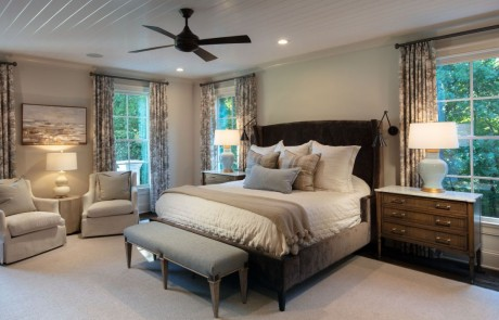 Neutral colored large master bedroom is painted in Benjamin Moore's Edgecomb Gray with custom trim work, white painted tongue-and-groove ceiling, secret hidden door, dark bronze wall sconces and ceiling fan, brown hardwood floors and designer finishes.