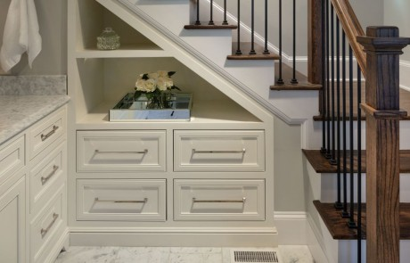 Under stair built-in custom cabinets with open shelving and chrome fixtures. New staircase with brown hardwood steps and black metal balusters.