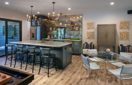 Modern Basement Remodel with Kitchen, Bar Island w/Seating, Charcoal Cabinets, Caesarstone Quartz Countertops, Stainless Steel Appliances, Mirrored Backsplash, Floating Shelves, Brass Pendant Lights, Panoramic Doors and Glass Game Table.