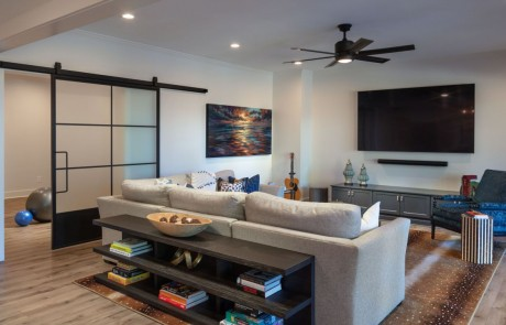 """Basement Remodel includes a Sophisticated Living Space with 85"""" TV and Comfortable Seating. Oversized Metal & Glass Sliding Doors lead to the Custom Home Gym."""