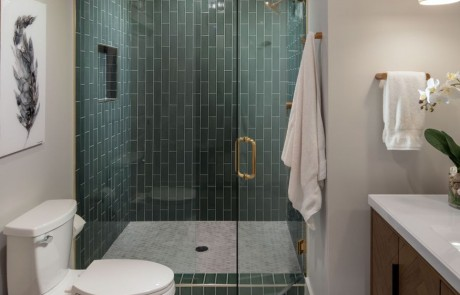 Basement Remodel includes a full bathroom with a sage colored, glass-tile, walk-in shower, and brushed gold accents. Hexagon, porcelain, tile flooring, brown, freestanding vanity, white marble countertops, undermount sink, and drop style pendants.