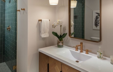 Midcentury style freestanding vanity with white marble countertops, undermount sink, gold hardware, rectangular gold mirror, and drop style pendants.