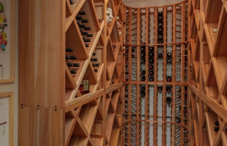 Basement Renovation with custom wine cellar is ideally located for climate and light control. The custom built-in shelving artfully displays our clients' wine collection.