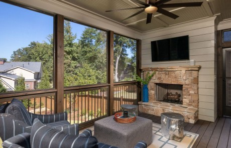 The screened in porch includes a stone fireplace with mounted tv, white shiplap walls, tongue and groove ceiling, brown ceiling fan and comfortable seating.