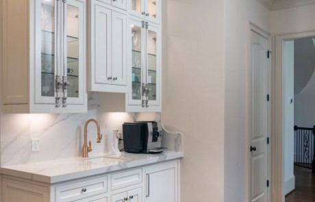 Separate custom beverage & coffee station features undermount sink with Waterstone pull down faucet in Satin Brass, white custom inset cabinets with decorative glass doors and brass Cremone bolt hardware, Kalos Bianco porcelain countertops, porcelain slab backsplash and undercabinet lighting.