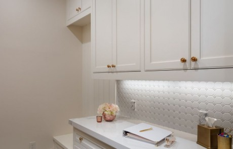 Mudroom remodel has a gray and white diamond pattern tile floor, white custom cabinets and built-ins with aged brass hardware, porcelain countertops and a matte white octagon mosaic backsplash.