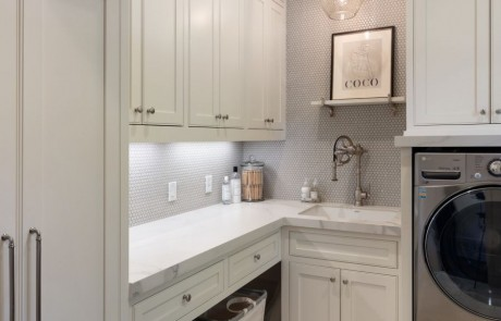 Custom Laundry Room with gray porcelain tile floor and penny round grey porcelain tile backsplash, white custom cabinets with floor to ceiling storage, solid surface countertops and undermount sink with Waterstone faucet.