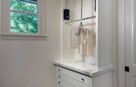 Custom Laundry Room with gray porcelain tile floor, white custom cabinets, solid surface countertops and custom hanging drying station and drying rack drawers.