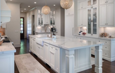 Custom Kitchen Remodel With White Custom Inset Cabinets with Decorative Glass Doors, Polished Kalos Bianco Porcelain Countertops, Kohler Apron Sink, Waterstone Luxury Faucet in Antique Brass, Antique Brass Crystal Chandelier Pendants, Oversized Island, Undercabinet lighting, and Brass Cremone Bolt Hardware